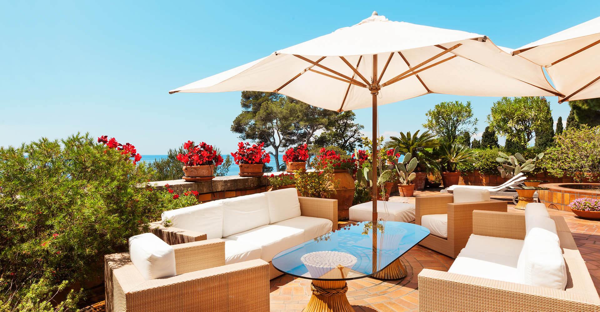 Sonnige Luxus-Terrasse mit weißen Möbeln und einem weißen Sonnenschirm