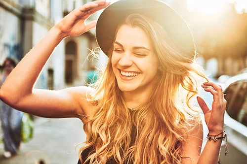 Frau mit gesunden Haaren und Hut lacht - Youtube