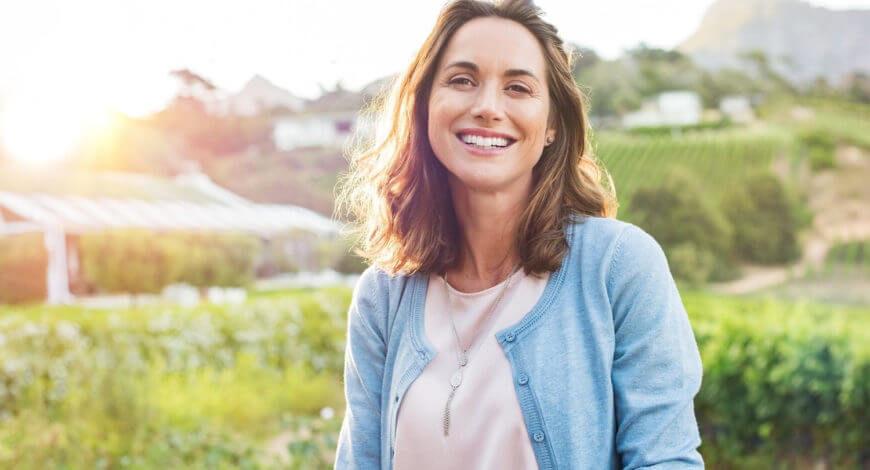 Weiblicher Coach lächelnd im Freiem, stellvertretend für die Wirkungen von gutem Stressmanagement