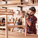 DiY-Heimwerker, der in Garage oder Werkstatt einen Holzstuhl schleift