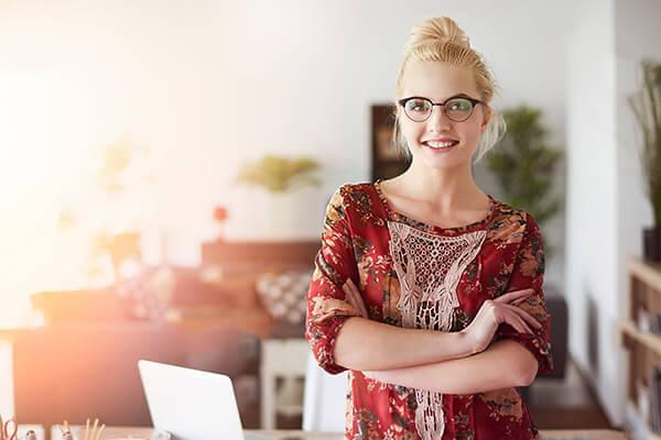 Lächelnde junge Dame, die von und für Zuhause beispielsweise als Innenarchitektin arbeitet