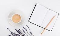 Ein Bleistift auf einem Notizbuch, das auf einem Tisch liegt neben einer Tasse Espresso und Lavendel-Blumen