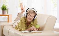 Eine junge Frau mit Kopfhörer und Kaffeetasse in der Hand, die auf einem Sofa liegt und ein Buch liest