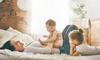 Mutter liegt gemeinsam mit 2 Kindern in Familienbett
