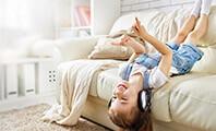 Ein Mädchen, das kopfüber auf dem Bett liegt und über Kopfhörer Musik hört