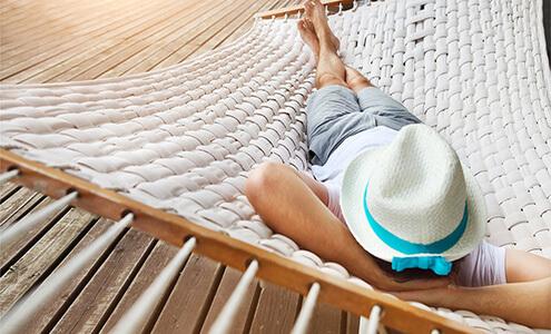 Eine große, weiß geflochtene Hängematte über einem Holzboden, auf der ein Mann mit Hut schläft oder entspannt.