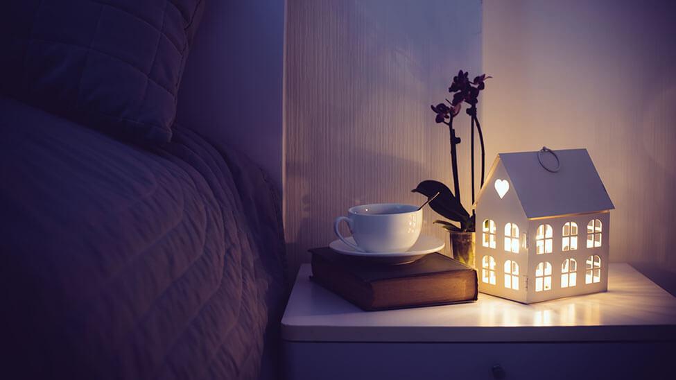 Buch, Tasse Tee und Kerzen neben dem Bett