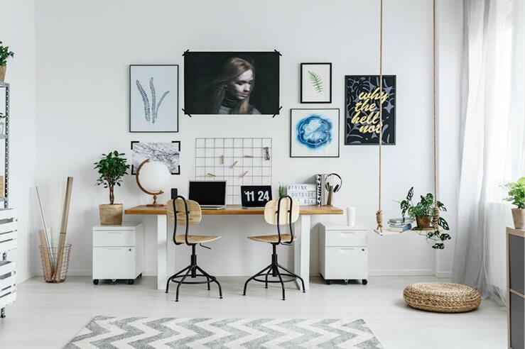 Helles Arbeitszimmer mit 2 Stühlen, Tisch und mehreren Bildern an der Wand