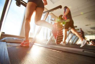 Frau läuft auf Cardiogerät Laufband