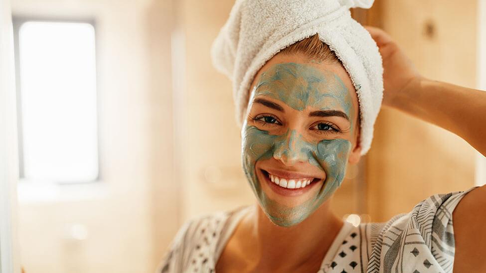 Frau macht Wellnesstag und lächelt mit Gesichtsmaske im Bad