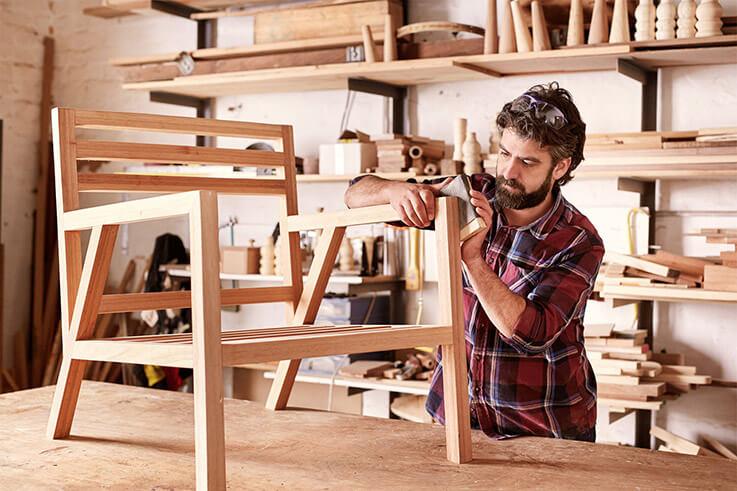 DiY-Handwerker, der einen selbstgefertigten Stuhl schleift