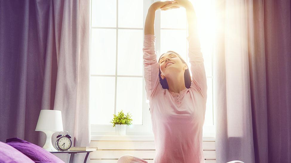 Junge Frau streckt sich freudestrahlend auf ihrem Bett nach Aufwachen