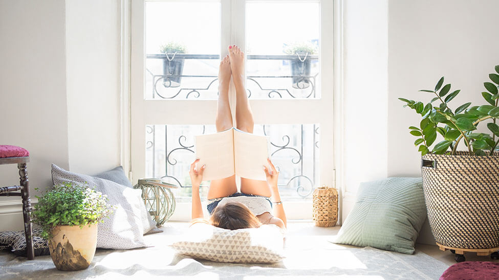 Junge Frau liegt entspannt am Fenster und liest ein Buch