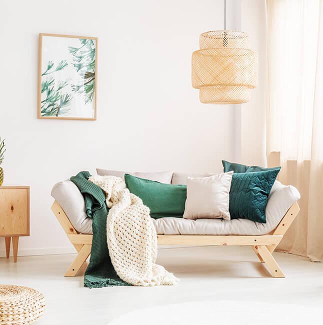 Einrichtung in smaragdgrünem Wohnzimmer - Couch, Kommode, dazu Bilder, Blumen und Bilder