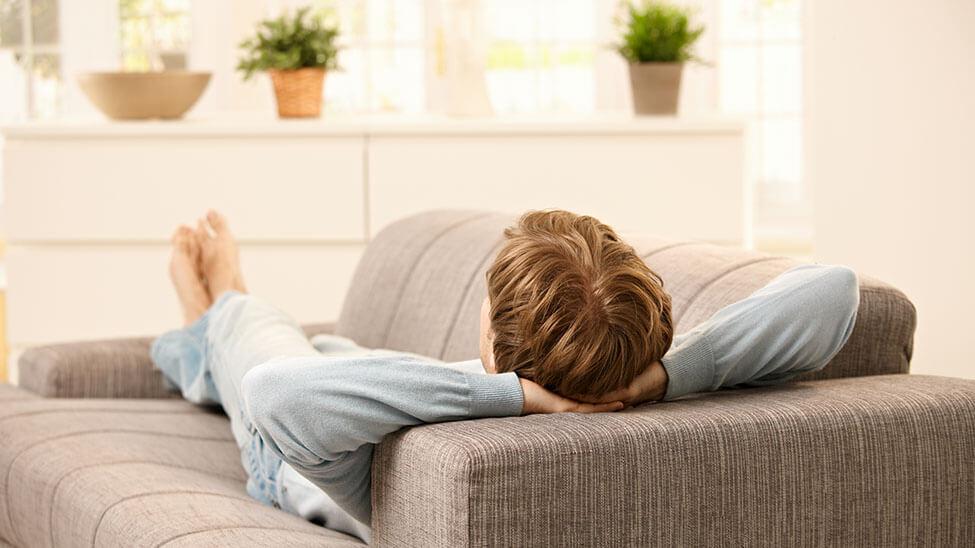 Junger Mann entspannt liegend auf Sofa im Wohnzimmer