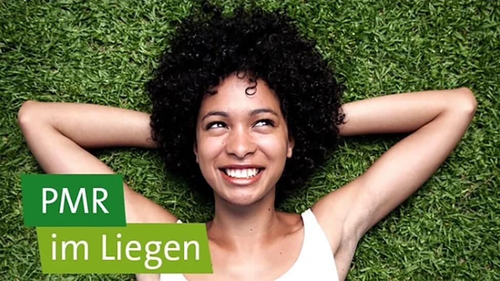 Frau liegt lächelnd auf dem Rasen mit PMR im Liegen als Slogan darüber