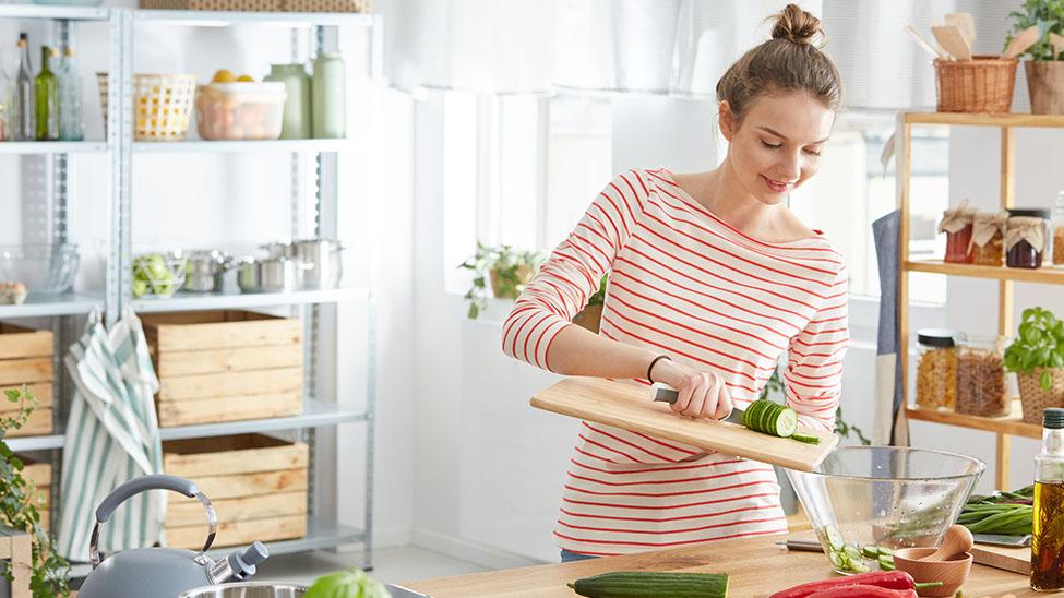 Frau macht sich einen Salat in der Küche