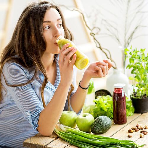 Junge Frau trinkt einen gesunden Smoothie aus Obst und Gemüse
