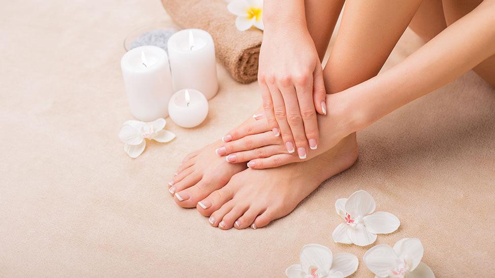 Frau pflegt ihre Füße - nur diese sind zu sehen zusammen mit Blüten, einem Handtuch und Kerzen