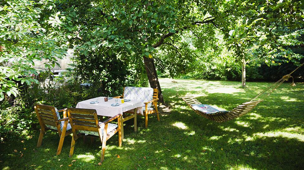 Grüner, weitläufiger Garten, in dem sich ein Tisch, mehrere Stühle und eine Hängematte befinden
