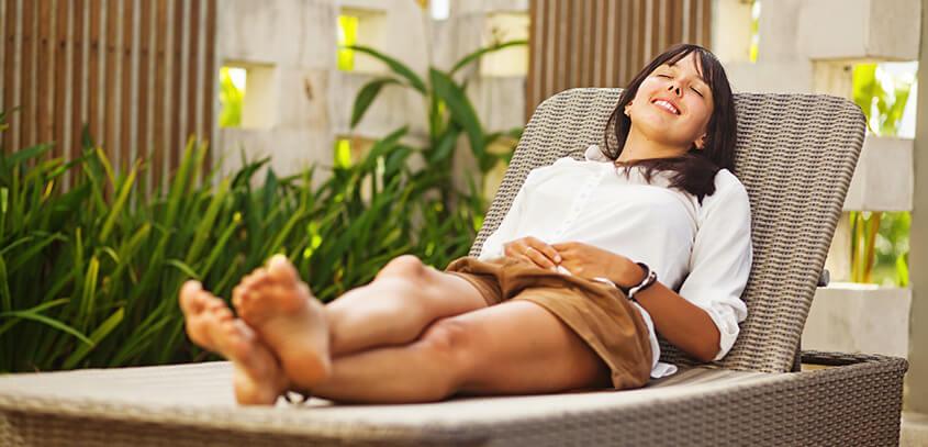 Frau entspannt auf Liege im Garten