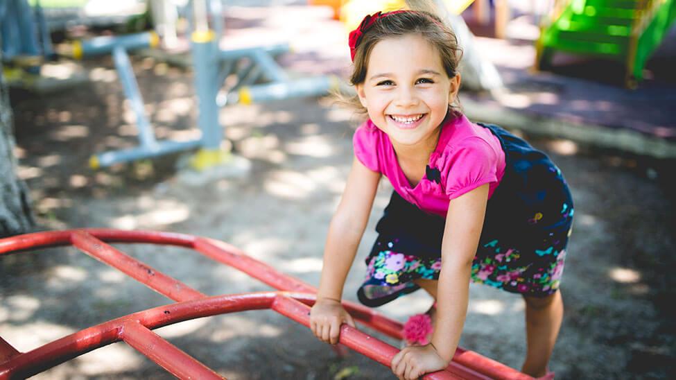 Mädchen spielt auf Klettergerüst während Kindergeburtstag