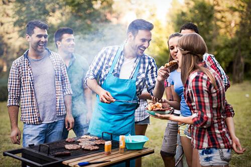 Freunde, die draußen im Garten vor einem Grill sich entspannt miteinder unterhalten, lachen und Spaß haben