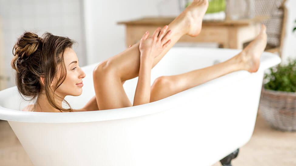 Junge Frau pflegt ihren Körper in Badewanne