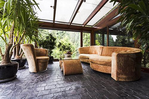 Nobler Kaltwintergarten mit Sofa, Glastisch und großen Pflanzen