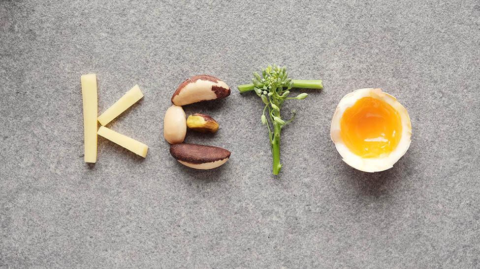 Der Begriff Keto dargestellt durch Kartoffel-Sticks, Nüsse, Grünzeug und ein Ei