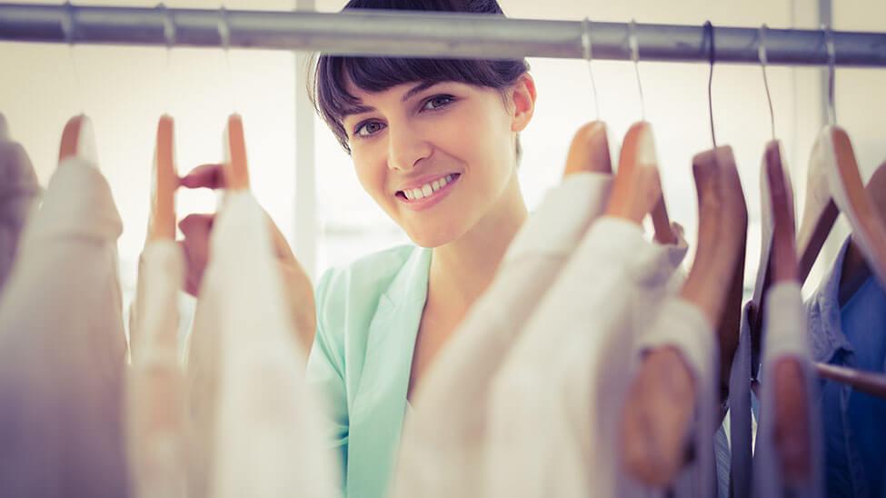 Junge Frau räumt ihren Kleiderschrank auf