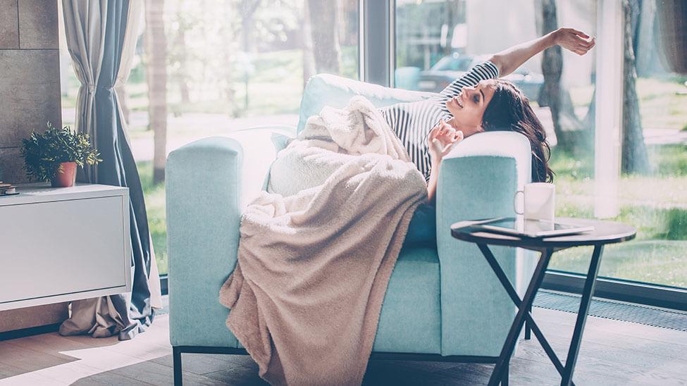 Frau streckt sich freudestrahlend in Sessel im lichtdurchflutetem Wohnzimmer
