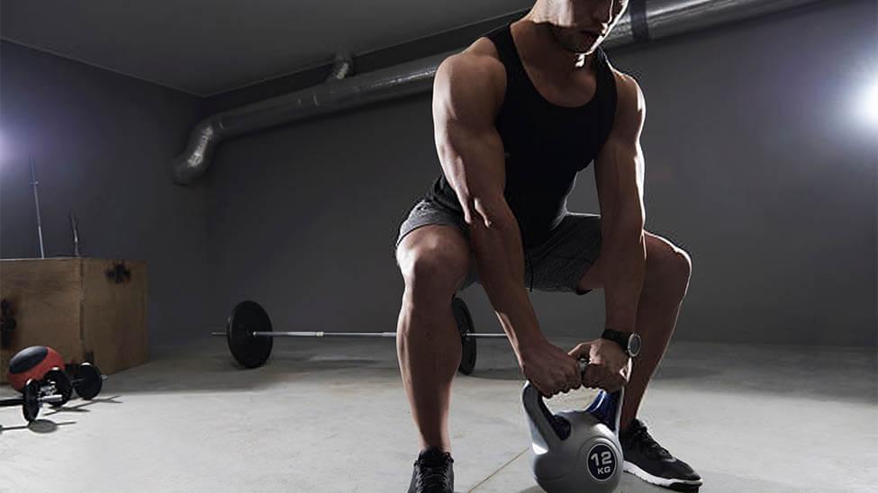 Muskulöser Mann führt die Kraftsport Übung Kniebeugen durch