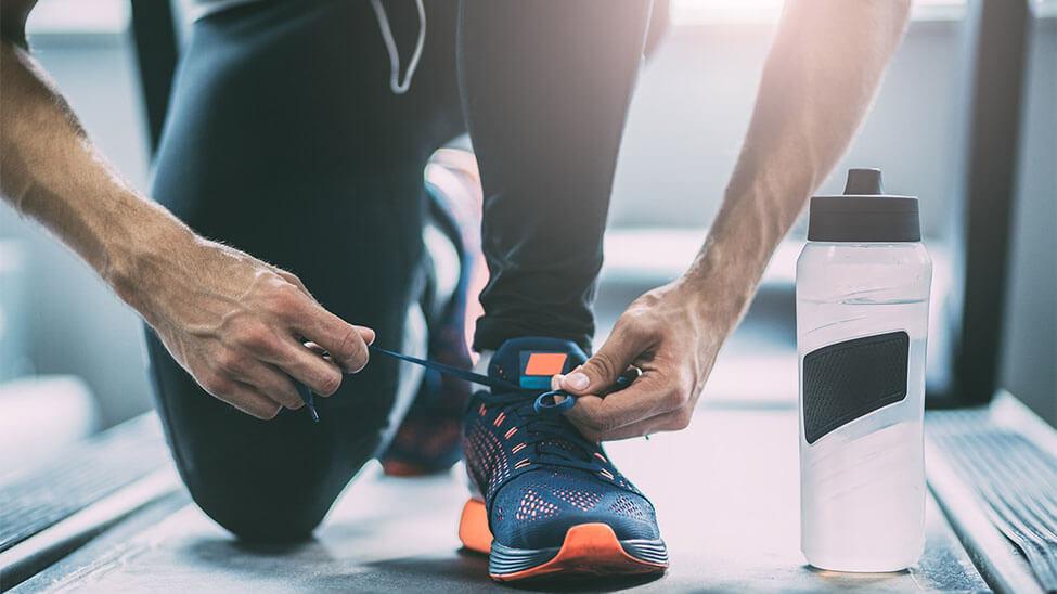 Mann schnürt sich Schuhe auf Laufband zuhause