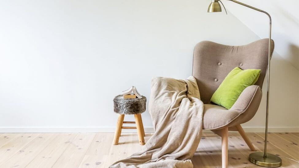 Leseecke mit Lesesessel, Kissen, Beistelltisch, Lampe und Decke