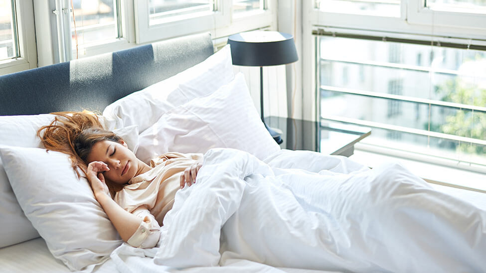 Frau liegt kurz vorm Aufwachen im Bett mit einem Lächeln auf dem Gesicht