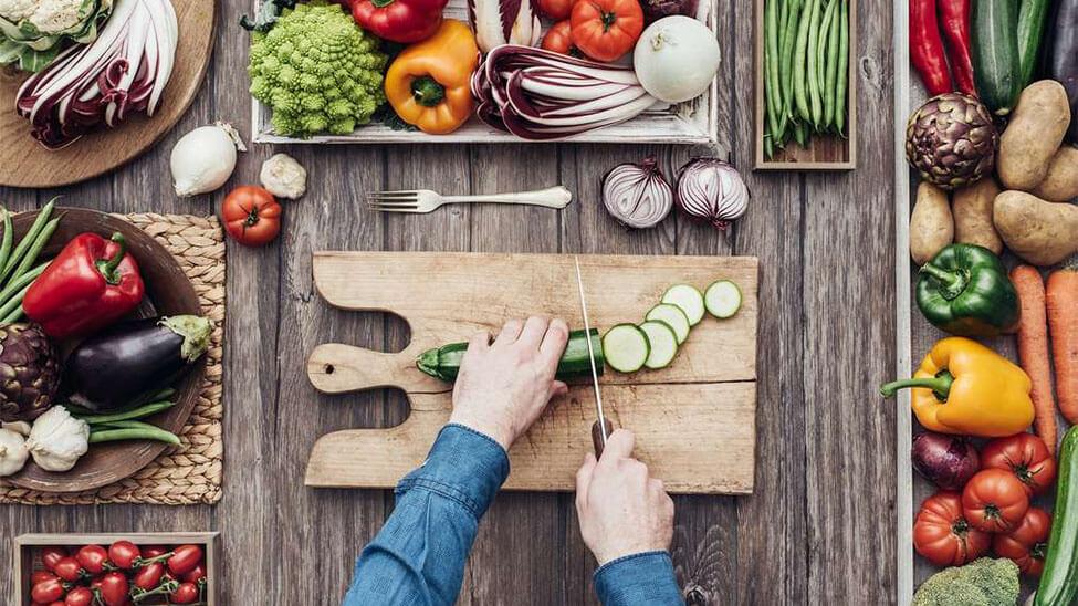 Frau schneidet Gurke neben vielen anderen Gemüsesorten für veganes Meal Prep