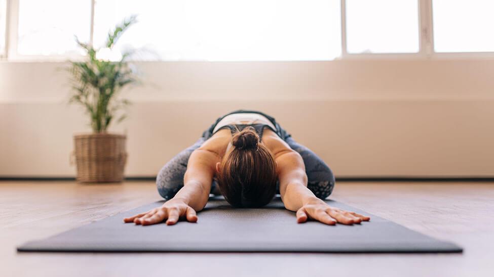 Frau streckt sich auf Matte in Meditationsraum