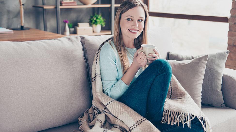 Frau wärmt sich mit Decke und Tasse Tee zuhause auf dem Sofa