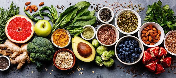 Dunkler Tisch mit verschiedensten Arten von Obst & Gemüse von oben fotografiert