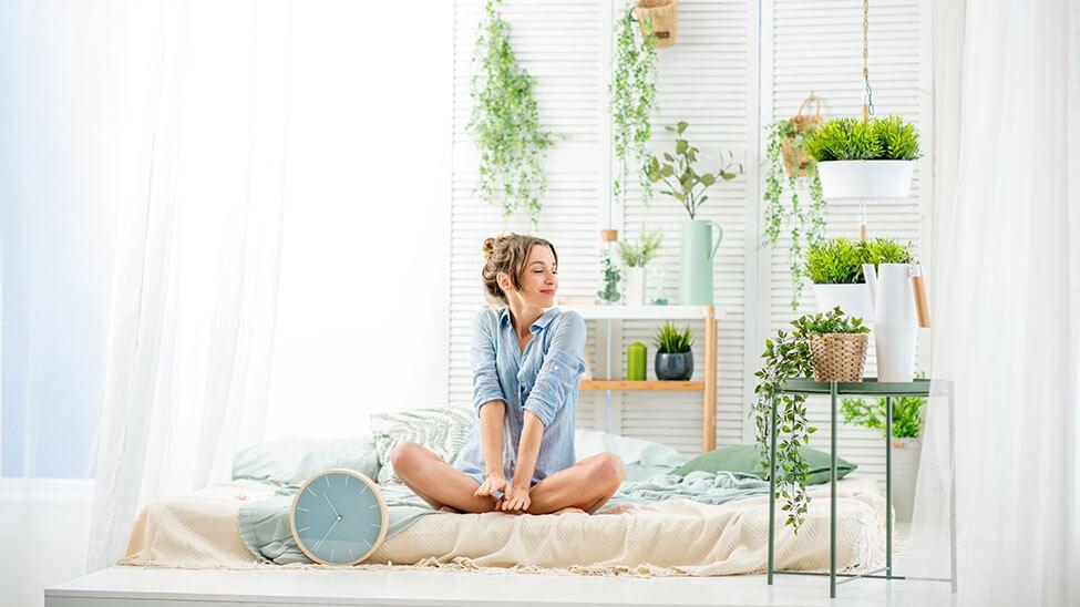Frau genießt die Luft in ihrem Schlafzimmer voller Pflanzen
