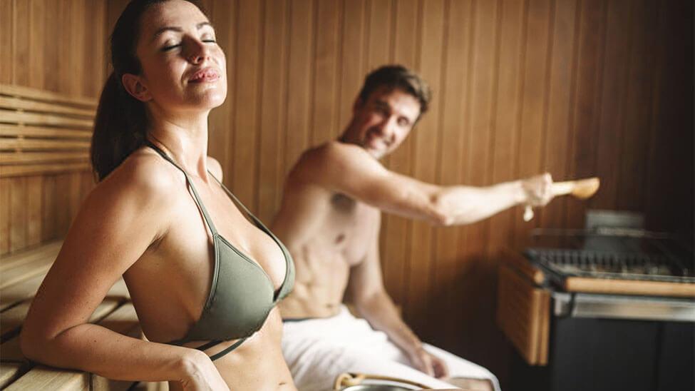 Frau entspannt in Sauna und ein Mann macht im Hintergrund einen Aufguss