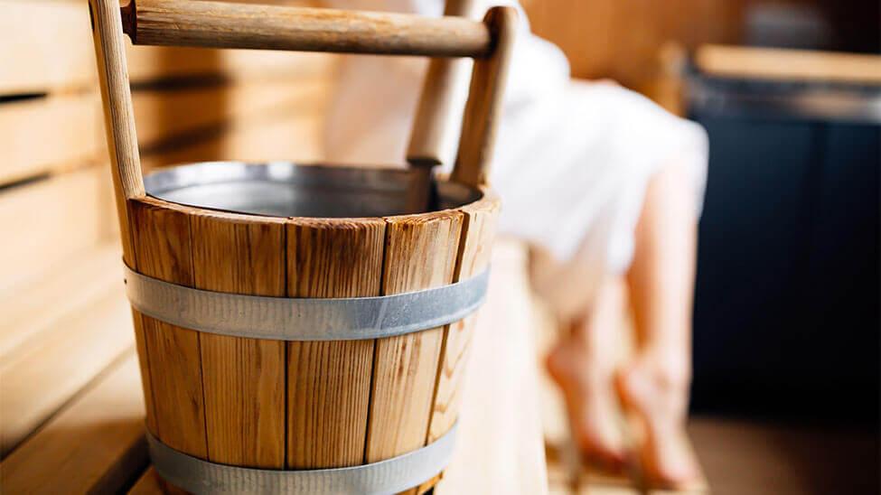 Eine Bottich mit Kelle drin als Saunazubehör in der Sauna