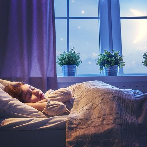Kind schläft im Bett am Fenster bei Mondschein