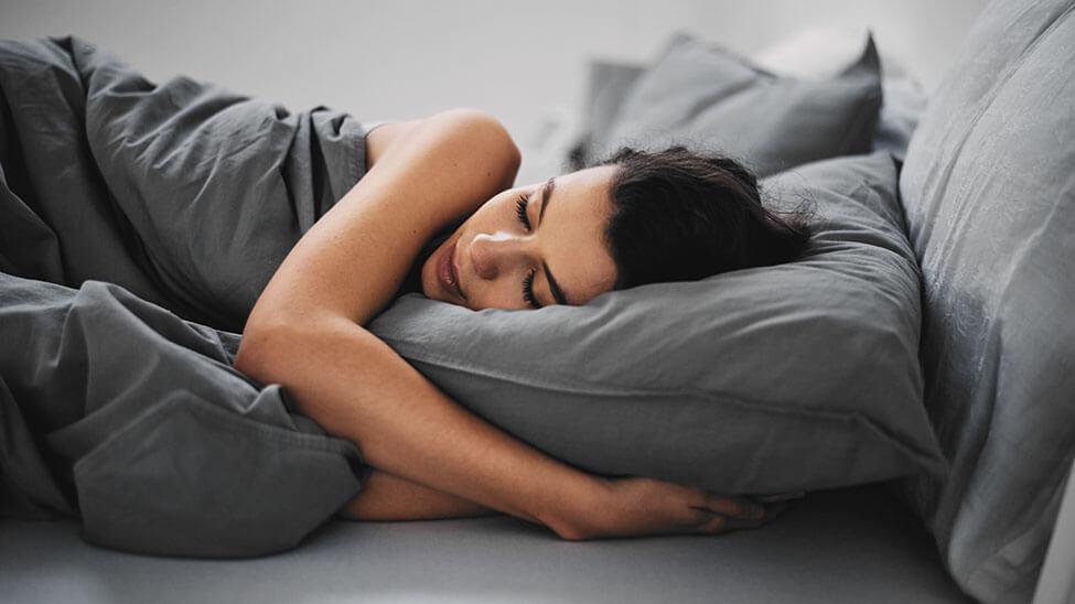 Frau schläft zufrieden im Bett