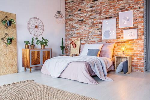 Helles Schlafzimmer mit Bett, Bildern und Pflanzen in rot-braun gehalten