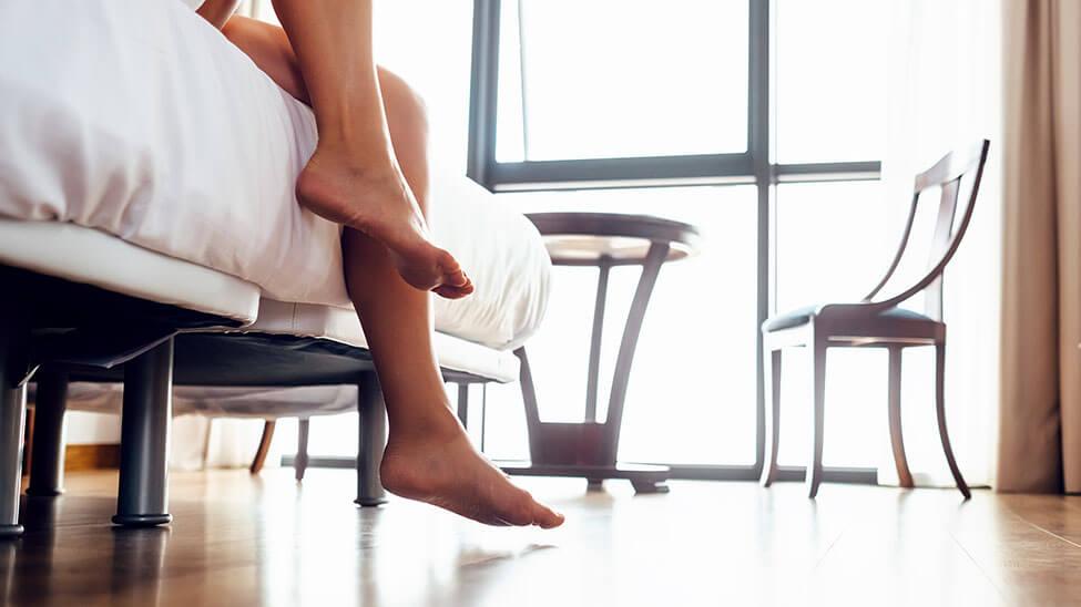 Frau steht morgens auf - man sieht nur das Bett und die Füße im Schlafzimmer