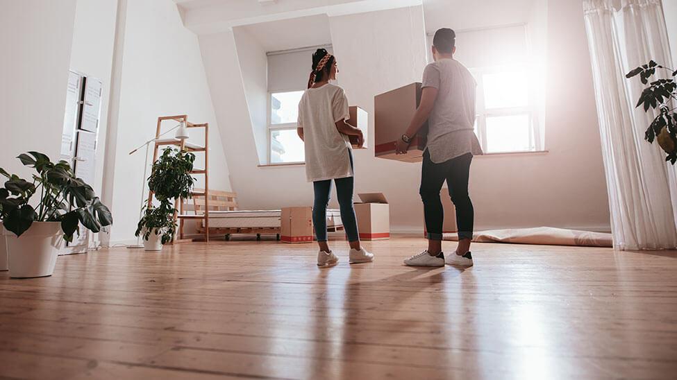 Junges Paar stellt im Wohnzimmer Möbel um