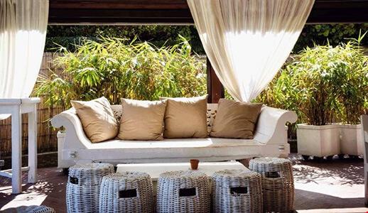 Terrasse mit großer Couch, Rattankörben, vielen Sträuchern im Hintergrund und weißen Vorhängen davor