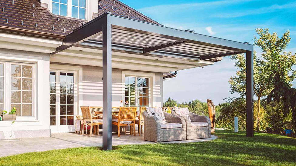 Terrassenüberdachung von vorne mit Terrassenmöbeln dadrunter und großem Garten drumherum